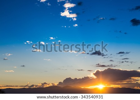 Scenic view of a beautiful sunset with blue sky and clouds over the mountains - stock photo