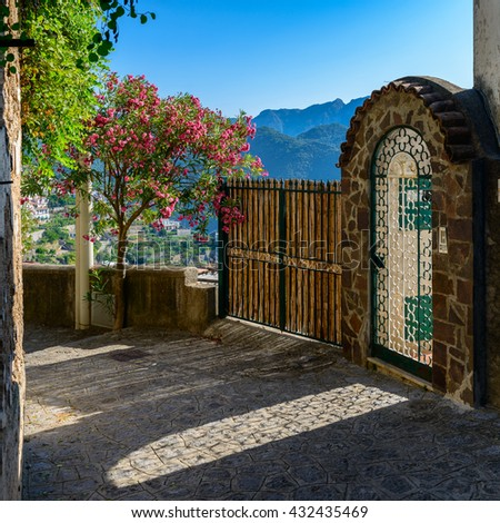 Scenic view of a garden door with blooming trees overlooking the hillside in Ravello, Campania, Italy. - stock photo