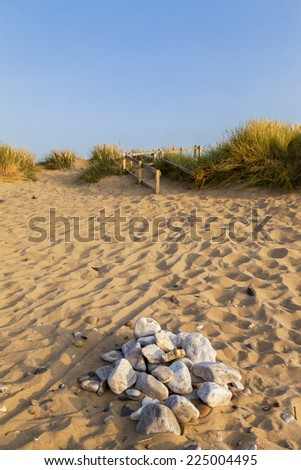 Scenic view of a golden sandy beach in the summer evening light . A pile of Pebbled stones in  the foreground, gold and green grasses  on the hill, blue sky.    - stock photo