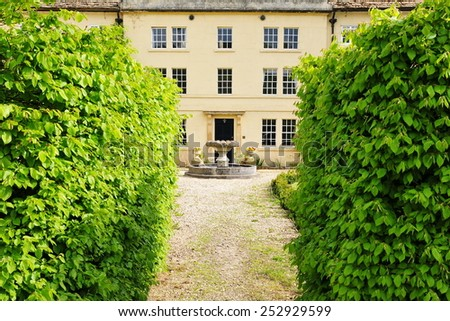 Scenic View of a Hedge Lined Path Leading to a Beautiful Victorian Era English Country House - stock photo