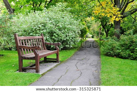 Scenic View of a Pathway and Wooden Bench in a Beautiful Leafy Landscape Garden - stock photo