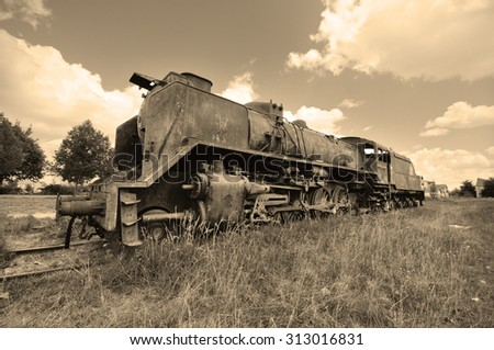 Scenic view of a vintage style picture of an ancient abandoned locomotive.