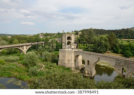 Scenic view of ancient and new bridges across Fluvia River in medieval town Besalu, Catalonia, Spain.