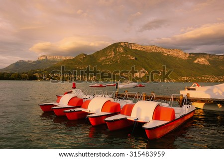 Scenic view of Annecy lake (Haute-Savoie, France) during golden sunset and water pedalos at foreground. - stock photo