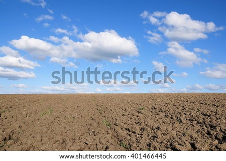 Scenic View of Bare Earth with a Beautiful Blue Cloudy Sky Above - stock photo
