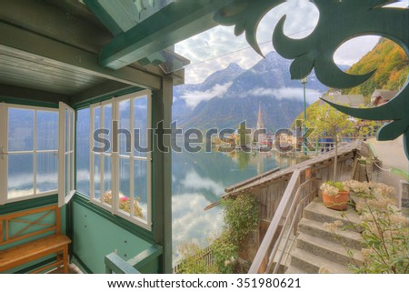 Scenic view of beautiful Hallstatt through the window with lakeside village and mountains reflected on the smooth lake water in beautiful Salzkammergut Region of Austrian Alps - stock photo