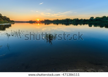 Scenic view of beautiful sunset above the river at summer evening