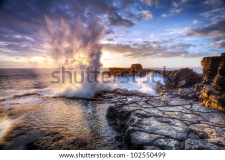 Scenic view of blowhole on rocky coastline with sunset cloudscape, Reunion Island, region of France. - stock photo
