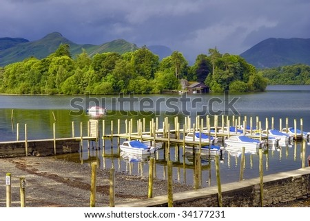 Scenic view of boats moored in small harbour on Derwent Water, Lake District National Park, Cumbria, England. - stock photo
