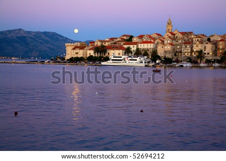 Scenic view of city of Korcula in Croatia with rising full moon - stock photo