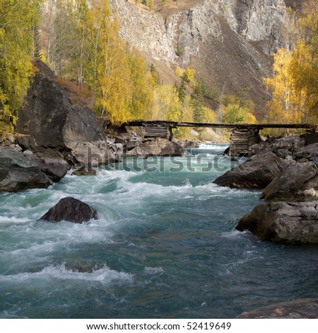 Scenic view of cold river and old wooden bridge - stock photo
