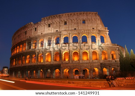 Scenic view of Coliseum or Colosseum amphitheatre in Rome with traffic light motion blurs in foreground, Italy.