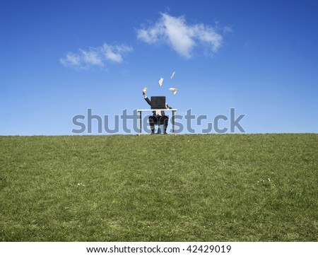 Scenic view of frustrated businessman working at desk in field, throwing papers. - stock photo