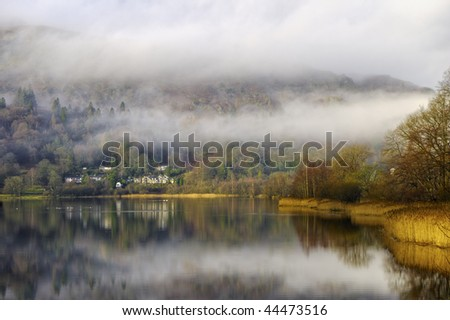Scenic view of Grasmere lake shrouded in mist, Lake District National Park, Cumbria, England. - stock photo