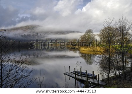 Scenic view of Grasmere Lake shrouded in mist with boat in foreground, Lake District National Park, Cumbria, England. - stock photo