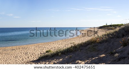 Scenic view of  grassy dunes   Ocean Beach, Bunbury, Western Australia on a sunny early morning in autumn  with the tide ebbing away leaving the sandy beach  with waves lapping gently on the shore. - stock photo