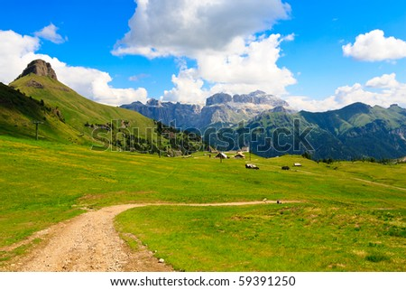 Scenic view of green plateau in high mountains with hotels and ski lift. - stock photo