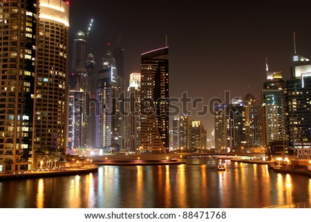 Scenic view of illuminated of Dubai city at night with boats, United Arab Emirates