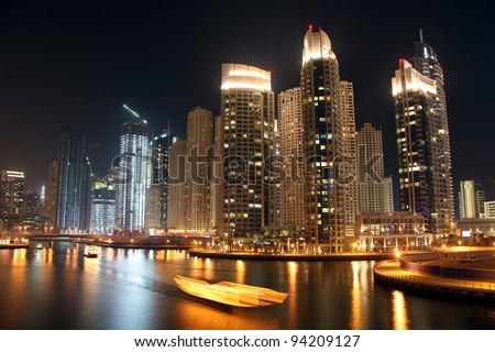 Scenic view of illuminated of Dubai city at night with boats, United Arab Emirates - stock photo