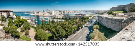 Scenic view of Marseille from height, France. Panorama of Marseilles with its harbor and variety of yachts, city road, old and modern buildings. Densely populated city with lots of historical places. - stock photo