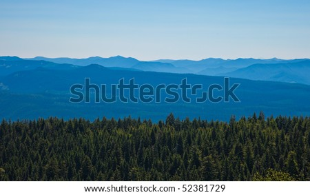 Scenic view of mountains with forest in foreground - stock photo