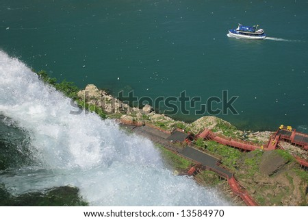 Scenic view of Niagara falls with boat full of tourists going to see the Horseshoe Bend falls past the Bridal Veil falls - stock photo
