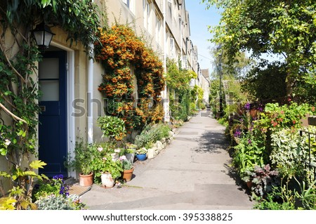 Scenic View of Old Terraced Cottages and a Beautiful Leafy Walkway in Rural England - stock photo