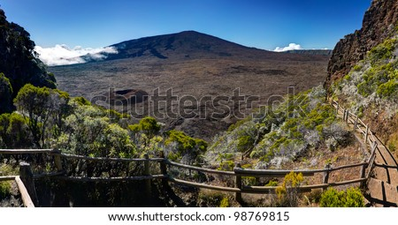 Scenic view of Piton de la Fournaise volcano viewed from the caldera with a track in foreground, Reunion Island National Park.