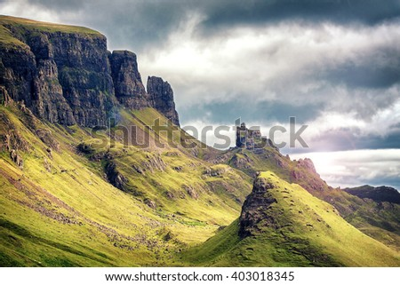 Scenic view of Quiraing mountains, with dramatic sky in the Isle of Skye, Scottish highlands, United Kingdom. Cinematic style processing with lens flare. - stock photo