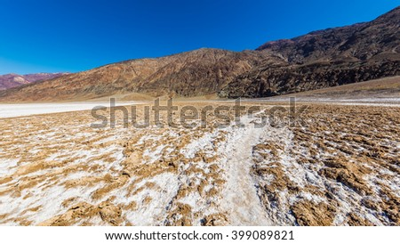 Scenic view of salt planes. The bottom of the dried-up salt sea. Salt crystals expand, pushing the crust of salt into rough, chaotic forms. Badwater Salt Flat, Death Valley National Park - stock photo