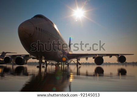 Scenic view of silhouetted passenger jet aircraft on flooded runway with sun in background, Don Mueang International Airport, Thailand. - stock photo