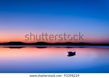 Scenic view of small fishing boat in calm water at sunset with hills in the background. - stock photo