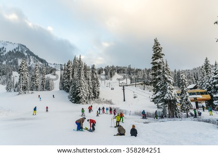 scenic view of small people around ski resort when sunset in snowy day.