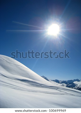 Scenic view of sun shining over snowy mountainside with ski tracks, Vars, France - stock photo