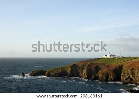 Scenic view of the coastline at Lizard Point, Lizard Peninsula, Cornwall with its historic lighthouse which marks the southernmost point in England overlooking the English Channel - stock photo