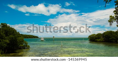 Scenic view of the Florida Keys with mangroves along the shoreline and a boat entering the harbor. - stock photo
