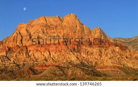 Scenic view of the moon shining over Red Rock Canyon, Nevada at sunrise - stock photo