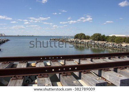 Scenic view of  the old rusted  historic unused railway line spanning the Leschenault Estuary at the flood gates  where it enters the Outer Harbour, Bunbury, Western Australia  on a fine spring day.