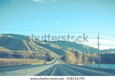 scenic view of the road with mountain background in vintage style. - stock photo