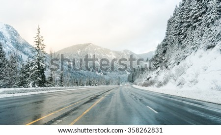 scenic view of the road with snow and mountain background in winter season ,vintage style. - stock photo