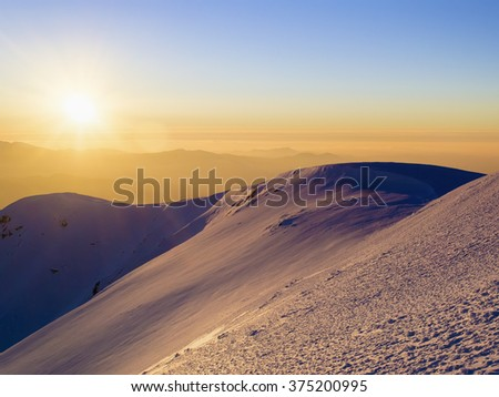 Scenic view of the sunset in the winter mountains. Direct sunlight. Sun rays. Light reflected from the snow. Clear sky. Deep shadows. Ukraine - stock photo