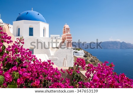 Scenic view of traditional cycladic houses with flowers in foreground, Oia village, Santorini, Greece - stock photo