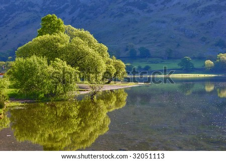 Scenic view of trees reflecting on Lake Ullswater, Lake District National Park, Cumbria, England. - stock photo