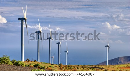 Scenic view of turbines on wind farm in countryside with sea and cloudscape background. - stock photo