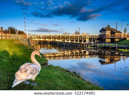 Scenic view of Winnington swing bridge, Northwich at dusk with a young mute swan in the foreground.