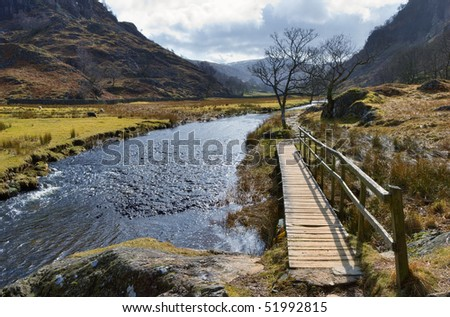 Scenic view of wooden walkway alongside Watendlath Beck with mountains in background, Lake District National Park, Cumbria, England. - stock photo