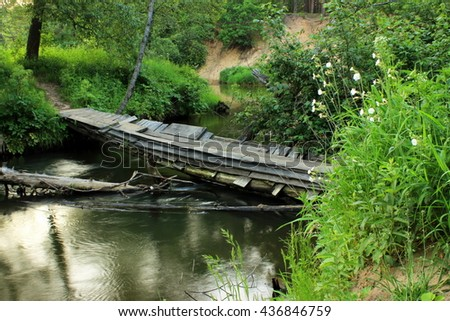 Scenic view on small river in a lush, forbidden environment with old shabby bridge over the water / Tranquil river flowing in a lush summer forest, reflection of plants in a water - stock photo