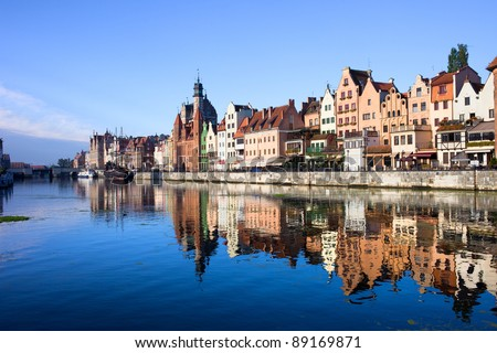 Scenic view with reflection on water of the Old Town of Gdansk in Poland by the Motlawa river - stock photo