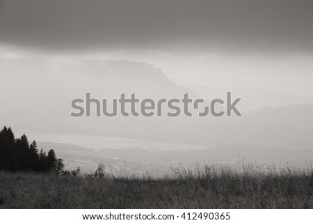 Scenic view with silhouettes of Alps mountains and a valley in gloomy autumn evening. Annecy lake area (Haute-Savoie, France). Black and white photo. - stock photo