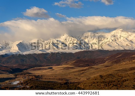 Scenic view with the beautiful mountain peaks with snow and glaciers, blue sky, clouds and the valley in the sunlight at sunrise
